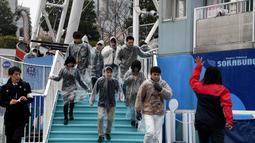 Instruktur memberikan bimbingan pelatihan kepada peserta yang mengikuti simulasi evakuasi anti-rudal di taman hiburan Tokyo Dome City, Jepang, (22/1). (AFP Photo/Toshifumi Kitamura)
