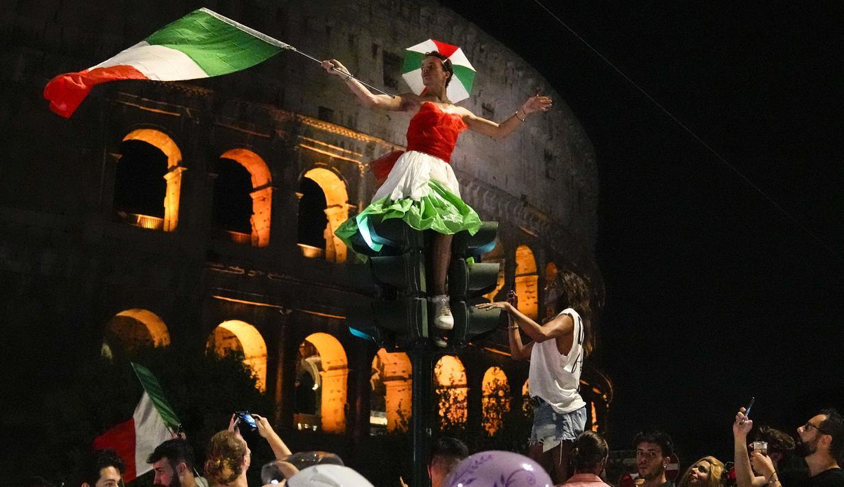 Pendukung Italia merayakan kemenangan di Roma, Italia pada Senin (12/07/2021), setelah Italia berhasil mengalahkan Inggris pada Final Euro 2020 yang berlangsung di Stadion Wembley, London, Inggris. Italia mengalahkan Inggris 3-2 dalam adu penalti setelah bermain imbang 1-1. (AP/Alessandra Tarantino)