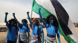 """Warga Palestina bergaya seperti karakter dari film """"Avatar"""" mengibarkan bendera selama protes menuntut hak untuk kembali ke kampung halaman mereka di perbatasan Israel-Gaza, Timur Khan Yunis di Gaza selatan Strip, (4/5). (AFP Photo/Said Khatib)"""