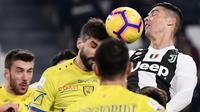 Bek Chievo, Luca Rossettini penyerang Juventus, Cristiano Ronaldo duel udara pada laga pekan ke-20 Serie A di Allianz Stadium, Senin (21/1). Juventus berhasil memantapkan posisi di puncak klasemen setelah menggilas Chievo 3-0. (Marco BERTORELLO/AFP)