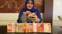 Petugas menunjukkan uang kertas rupiah di Bank BUMN, Jakarta, Selasa (17/4). Rupiah siang ini melemah dibandingkan tadi pukul 09.00 WIB di level Rp 13.771 per dolar AS. (Liputan6.com/Angga Yuniar)