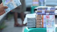 Penjual jasa penukaran uang pecahan menunggu konsumen di Jalan Otista Raya di Karawaci, Kota Tangerang, Senin (10/5/2021). Penjual jasa penukaran uang baru musiman tersebut mulai bermunculan menjelang lebaran yang dikenakan tarif jasa sebesar 10 persen. (Liputan6.com/Angga Yuniar)