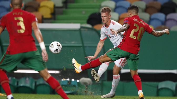 Gelandang Spanyol, Dani Olmo mengumpan bola dari kawalan pemain Portugal, Joao Cancelo pada pertandingan persahabatan di stadion Jose Alvalade di Lisbon, Rabu (7/10/2020). Spanyol bermain imbang 0-0 atas Portugal. (AP Photo/Armando Franca)