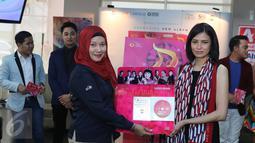 Linda Wibisono, Head of Local Acquisition Department Indosiar (kiri) memberikan pelakat ke pihak Trinity Optima Production yang di wakilkan oleh Rizki Utami usai peluncuran VCD Karaoke di Jakarta, Kamis (6/10). (Liputan6.com/Herman Zakharia)