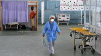 Seorang dokter Tunisia merawat seorang pasien di gym yang diubah untuk menangani lonjakan infeksi COVID-19 di pusat kota Kairouan pada 4 Juli 2021. Tunisia tengah berjuang menghadapi tsunami COVID-19 sementara jumlah orang yang meninggal akibat virus corona terus melonjak tinggi. (FETHI BELAID/AFP)