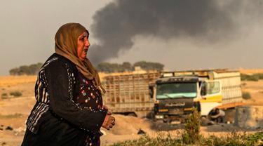 Seorang wanita berjalan saat asap mengepul menyusul pemboman Turki di Kota Ras al-Ain, Provinsi Hasakeh, Suriah, Rabu (9/10/2019). Turki mulai menggelar operasi militer untuk menyasar milisi Kurdi di utara Suriah. (Delil SOULEIMAN/AFP)