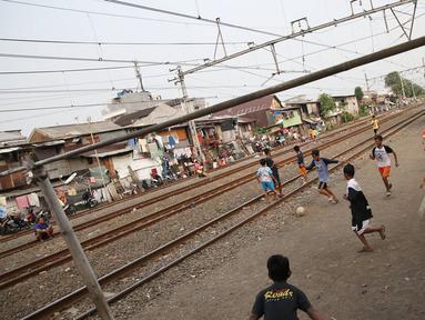 Suasana di pinggir rel kereta api di kawasan Kemayoran, Jakarta, Senin (24/7). Minimnya lahan bermain menyebabkan anak-anak terpaksa bermain di lokasi tersebut, meskipun berbahaya bagi keselamatan. (Liputan6.com/Immanuel Antonius)
