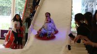 Ekspresi seorang anak berseluncur di perosotan es di Lippo Mal Puri, Jakarta, Jumat (22/12). Jelang Natal banyak pusat perbelanjaan mendekor bangunannya bernuansa natal untuk menarik daya tarik minat masyarakat. (Liputan6.com/Angga yuniar)