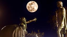Fenomena super snow moon terlihat di antara patung Alexander Agung (kanan) dan Diogenes of Sinope (kiri) di Corinth, Yunani, Selasa (19/2). Super snow moon menampakkan diri di berbagai belahan dunia. (Valerie GACHE/AFP)