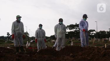Petugas melakukan pemakaman dengan prosedur Covid-19 di TPU Tegal Alur, Jakarta, Minggu (3/12/2021). TPU khusus jenazah Covid-19 di Pondok Ranggon telah terisi penuh, baik untuk jenazah muslim maupun nonmuslim. (Liputan6.com/Angga Yuniar)