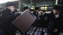 Rombongan grup orkestra Korut merapihkan koper saat tiba di kantor transit Korea di DMZ di Paju (5/2). Korut mengirim rombongan seni Samjiyon beranggota 140 orang ke Selatan untuk dua konser di ibukota Seoul dan di Gangneung. (AFP Photo/Pool/Jung Yeon-Je)