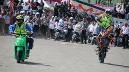 Aksi freestyle motor selama kegiatan Millenial Road Safety Festival Gorontalo, Minggu (10/2). Atraksi freestyle digelar di Lapangan Taruna Remaja Kota Gorontalo. (Liputan6.com/Rahmad Arfandi Ibrahim)