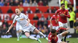 Pemain Swansea City, Sam Clucas (kiri) kesakitan saat di jegal pemain Manchester United, Victor Lindelof pada laga Premier League di Old Trafford, (31/3/2018).  Manchester United menang 2-0. (Anthony Devlin/PA via AP)