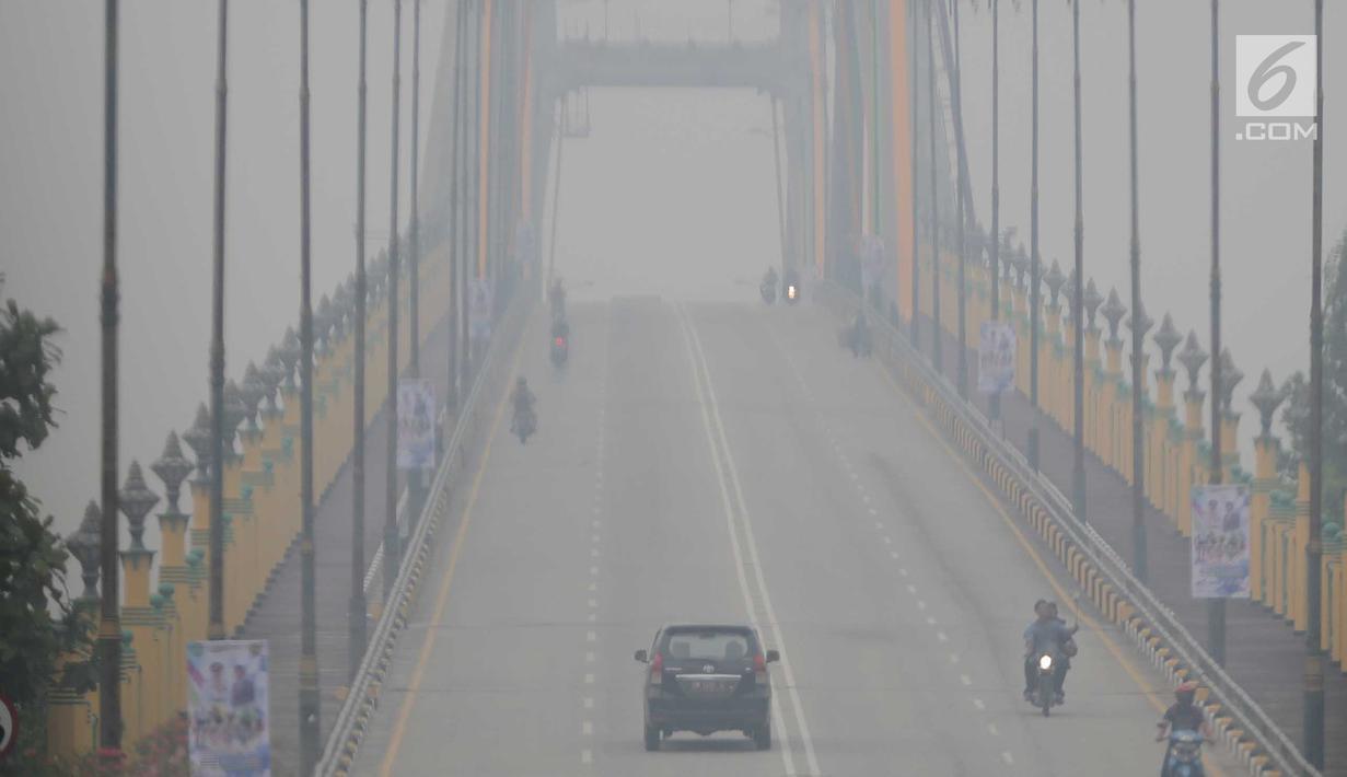 Sejumlah kendaraan melintas di atas jembatan yang diselimuti kabut asap di Kota Pekanbaru, Riau, Selasa (10/9/2019). Kabut asap akibat kebakaran hutan dan lahan (karhutla) tersebut menurunkan jarak pandang dan kualitas udara turun ke status tidak sehat. (Liputan6.com/Faizal Fanani)