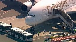 Petugas tanggap darurat berkumpul di luar pesawat setelah penumpang Emirates Airline dilaporkan jatuh sakit di Bandara Kennedy New York, Rabu (5/9). Sekitar 100 orang mengeluh sakit selama berada di pesawat dengan nomor penerbangan 521. (WABC 7 via AP)