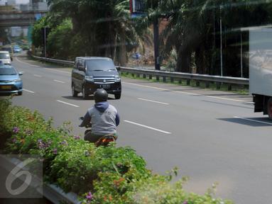 Seorang pengendara motor nekat melawan arus lalu lintas di Tol Cengkareng, Banten, Selasa (22/8). Diduga pengendara ini motor salah membaca rambu jalan, aksi ini terjadi sekitar pukul 13.00 WIB. (Liputan6.com/Helmi Fithriansyah)