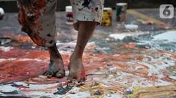 """Sadikin Pard (53) membuat karya lukisan dengan kedua kakinya saat Indonesian Art Festival """"Pesta Seni Rupa Indonesia"""" di Museum Nasional, Jakarta, Minggu (10/11/2019). Sadikin Pard membuktikan karyanya yang telah merambah ke kancah internasional. (merdeka.com/Iqbal S. Nugroho)"""