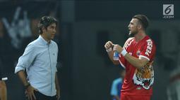 Pemain depan Persija, Marko Simic (kanan) berbincang dengan pelatih Stefano Cugurrausai kaus yang dikenakan robek pada bagian lengan saat laga melawan Selangor FA di Stadion Patriot Candrabhaga, Bekasi, Kamis (6/9). (Liputan6.com/Helmi Fithriansyah)