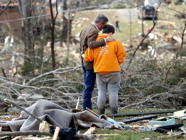 Gubernur Tennessee Bill Lee (kiri) berdoa bersama Kayla Cowen yang sedang mencari tetangganya setelah tornado menerjang Cookeville, Tennessee, Amerika Serikat, Selasa (3/3/2020). Tornado yang menerjang Tennessee menewaskan 25 orang. (AP Photo/Mark Humphrey)