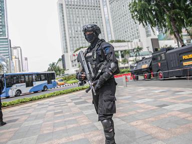 Petugas Brimob dengan senjata lengkap berjaga di kawasan Bundara HI, Jakarta, Kamis (24/12/2020). Jelang malam Natal dan perayaan Tahun Baru, pengamanan Ibu Kota diperketat untuk menjamin keamanan dan kenyamanan masyarakat. (Liputan6.com/Faizal Fanani)
