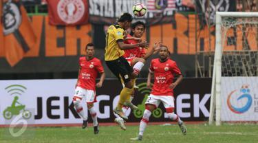 Pemain Persija Jakarta berebut bola di udara dengan pemain Barito Putera saat pertadingan Liga 1 di Stadion Patriot, Bekasi (22/4). Skor pada pertandingan antar Persija Jakarta kontra Barito Putera  tersebut 1-1. (Liputan6.com/Gempur M. Surya)