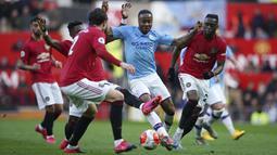 Penyerang Manchester City, Raheem Sterling, berusaha melewati pemain Manchester United pada laga Premier League di Stadion Old Trafford, Minggu (8/3/2020). Manchester United menang dengan skor 2-0. (AP/Dave Thompson)