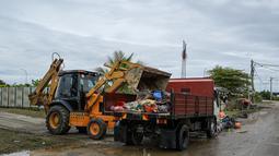 Sebuah ekskavator mengangkut puing-puing ke truk setelah air banjir surut di Mentakab, negara bagian Pahang Malaysia (11/1/2020). Tiga sungai di negara bagian itu - Sungai Lepar, Sungai Lipis dan Sungai Lembing - telah melewati tingkat bahaya. (AFP/Mohd Rasfan)