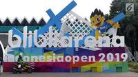 Pengemudi ojek online beristirahat di depan ornamen pintu masuk jelang pelaksanaan turnamen Indonesia Open 2019 di Istora Senayan, Jakarta, Senin (15/7/2019). Indonesia Open 2019 akan dihelat pada 16-21 Juli 2019. (Liputan6.com/Helmi Fithriansyah)