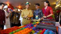 Presiden Joko Widodo (Jokowi) meninjau produk UMKM dalam kunjungan kerjanya di Sanur, Bali, Sabtu (23/6). Kunjungan kerja ini dalam rangka sosialisasi aturan baru terkait dengan Usaha Mikro Kecil dan Menengah (UMKM). (Liputan6.com/Pool/Biro Pers Setpres)