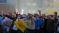 Suporter Leeds United merayakan keberhasilan timnya yang sukses kembali ke kompetisi Premier League di Elland Road, Leeds, Sabtu (18/7/2020). Leeds United dipastikan promosi ke Premier League musim 2020/2021 usai West Brom kalah 1-2 atas Huddersfield Town. (AFP/Paul Ellis)