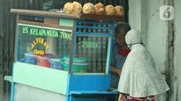 Pedagang sedang melayani pembeli di kawasan Jatinegara, Jakarta, Jumat (5/2/2021). Di tengah lonjakan kasus COVID-19 masih banyak masyarakat yang abai terhadap protokol kesehatan. (Liputan6.com/Herman Zakharia)