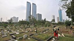 Petugas kebersihan memotong rumput makam di TPU Karet Bivak, Jakarta, Kamis (12/7). Kurang lebih 100 jenazah dimakamkan setiap harinya di wilayah Jakarta. (Merdeka.com/Iqbal Nugroho)