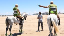 Sejumlah tentara berkuda yang berpatroli di sebuah pantai menyuruh pulang seorang pria di Sale, Maroko, pada 14 Juni 2020. Maroko pada 14 Juni 2020 mengumumkan 101 infeksi baru COVID-19, menambah jumlah kasus terkonfirmasi di negara Afrika Utara tersebut menjadi 8.793. (Xinhua/Chadi)
