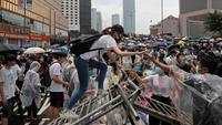 Seorang wanita memanjat paga saat bentrok dengan polisi anti huru hara di luar gedung Dewan Legislatif, Hong Kong, Rabu (12/6/2019). Polisi Hong Kong telah menggunakan gas air mata ke arah ribuan demonstran yang menentang RUU ekstradisi yang sangat kontroversial. (AP Photo/ Kin Cheung)