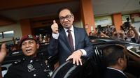 Anwar Ibrahim mengacungkan jempol kepada para pendukungnya di Rumah Sakit Rehabilitasi Cheras, Kuala Lumpur. Tindakan itu mengafirmasi statusnya sebagai orang yang bebas, usai menerima pengampunan dari Raja Malaysia (16/5) (Mohd Rasfan / AFP PHOTO)