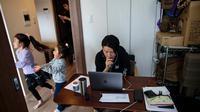Gambar pada 23 Maret 2020 menunjukkan seorang karyawan di sebuah perusahaan startup, Yuki Sato, bekerja dari rumah selama pandemi virus corona Covid-19  saat dua putrinya, Yurina dan Hinano bermain dan sang istri menggunakan ponsel di Tokyo. (Behrouz MEHRI / AFP)