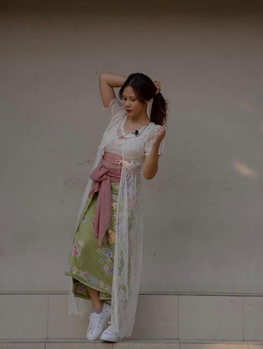 Kain batik hijau yang dipadukan dengan outer brokat dan belt berwarna pink membuat lookmu makin stunning. (Instagram/cakecaine).