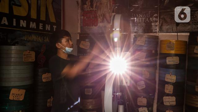 Adul (29) saat memutar film layar tancap di gudang rumahnya di Jakarta, Rabu (28/4/2021). Adul mengaku saat ini usahanya sedang istirahat, karena kondisi pandemi dan sebagian alat mereka yang