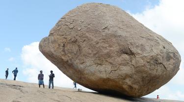 Pengunjung berdiri dekat batu 'Krishna's Butter Ball' yang terkenal di Mahabalipuram, India, Kamis (3/10/2019). Batu yang dikenal masyarakat sekitar dengan nama Vaan Irai Kal ini terletak di lereng dengan kemiringan 45 derajat. (ARUN SANKAR / AFP)