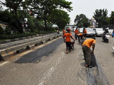 Sejumlah petugas mengaspal jalanan yang berlubang di Jalan Kramat Raya, Jakarta, Rabu (25/2/2015). Perbaikan jalan rusak pascabanjir terus dikebut Dinas Pekerjaan Umum (DPU) DKI Jakarta. (Liputan6.com/Faizal Fanani)