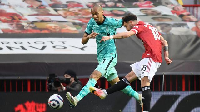 Gelandang Manchester United, Bruno Fernandes (kanan) melepaskan tendangan yang berbuah gol pertama timnya ke gawang Liverpool dalam laga lanjutan Liga Inggris 2020/2021 pekan ke-35 di Old Trafford, Kamis (13/5/2021). Manchester United kalah 2-4 dari Liverpool. (AFP/Michael Regan/Pool)