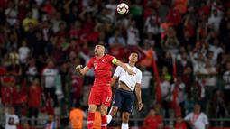 Striker Turki, Burak Yilmaz, duel udara dengan bek Prancis, Raphael Varane, pada laga kualifikasi Piala Eropa 2020 di Stadion Buyuksehir Belediyesi, Minggu (9/6). Turki menang 2-0 atas Prancis. (AFP/Bulent Kilic)