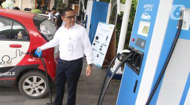 Karyawan PLN melakukan pengisian daya listrik pada salah satu kendaraan di Stasiun Pengisian Listrik Umum (SPLU) di PLN Gambir, Jakarta, Rabu (29/10/2019). Stasiun pengisian listrik tersebut tersebar di empat kota, yakni Tangerang, Bali Selatan, Jakarta, dan Bandung. (Liputan6.com/Angga Yuniar)