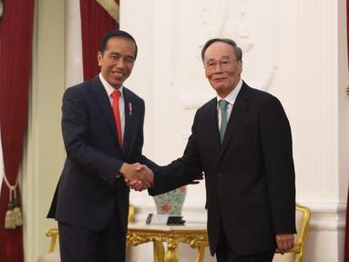 Presiden Joko Widodo atau Jokowi (kiri) bersalaman dengan Wakil Presiden China Wang Qishan saat menerima kunjungannya  di Istana Merdeka, Jakarta, Minggu (20/10/2019). Jokowi bertemu wakil presiden negara sahabat usai dilantik menjadi Presiden RI periode 2019-2024. (Liputan6.com/Angga Yuniar)