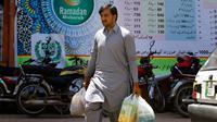 Seorang pria seusai membeli stok makanan di supermarket yang dikelola pemerintah Pakistan di Islamabad, Rabu (16/5). Warga berbelanja untuk memenuhi kebutuhan menyambut Puasa Ramadan yang dimulai pada Kamis (17/5). (AP/Anjum Naveed)