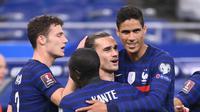 Penyerang Prancis, Antoine Griezmann (tengah) berselebrasi bersama rekan-rekannya saat laga kontra Ukrainan pada kualifikasi Piala Dunia 2022 di Stade de France, Kamis (25/3/2021) dini hari WIB. (AFP/Franck Fife)