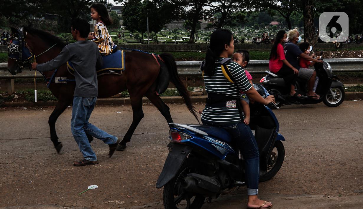 Seorang anak menaiki kuda di ruang kota Jalan Inpeksi Tanah Kusir, Jakarta, Senin (19/4/2021). Jalan Inpeksi Tanah Kusir ini menjadi salah satu tempat pilihan warga untuk menghabiskan waktu sembari menunggu berbuka puasa atau ngabuburit. (Liputan6.com/Johan Tallo)