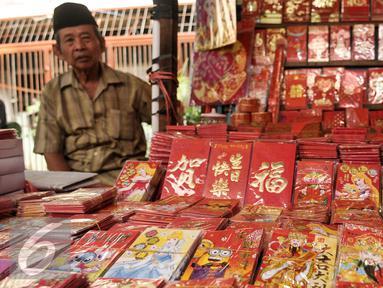 Pedagang angpao menunggu pembeli di kawasan Petak Sembilan, Jakarta, Senin (23/1). Jelang hari raya Imlek 2017 pedagang angpao dan pernak-pernik mulai ramai di kawasan Petak Sembilan. (Liputan6.com/Yoppy Renato)