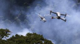 Sebuah helikopter berpartisipasi dalam operasi pemadaman kebakaran hutan di Koycegiz, Mugla, Turki, Senin (9/8/2021). Kebakaran hutan memaksa warga melarikan diri ke pantai untuk diselamatkan melalui laut. (AP Photo/Emre Tazegul)