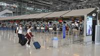Pelancong berjalan di ruang keberangkatan yang hampir kosong karena jumlah pengunjung menurun drastis di Bandara Suvarnabhumi di Bangkok, Rabu (11/3/2020). Di Thailand sendiri lebih dari 50 orang terinfeksi virus corona COVID-19 yang telah menggemparkan seluruh dunia. (Mladen ANTONOV/AFP)